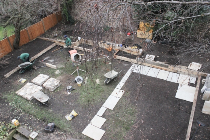New fence, sleepers outlining borders, and paving outlining patio is in place, with small bed at the top of the patio